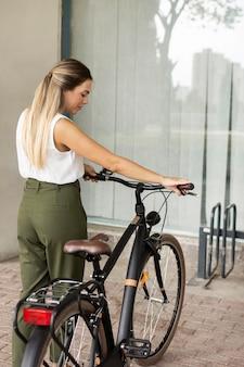 Mulher com tiro médio segurando o guidão da bicicleta