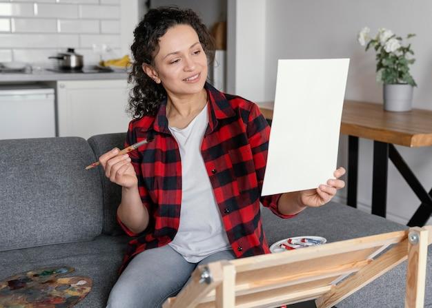 Mulher com tiro médio segurando papel