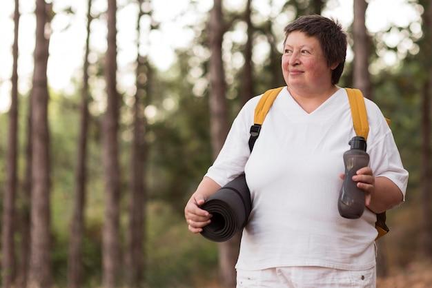 Mulher com tiro médio segurando tapete de ioga