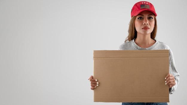 Mulher com tiro médio segurando um cartaz vazio