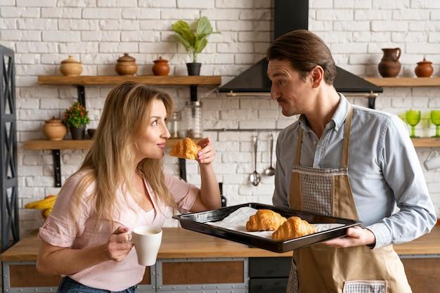 Mulher com tiro médio segurando um croissant Foto gratuita