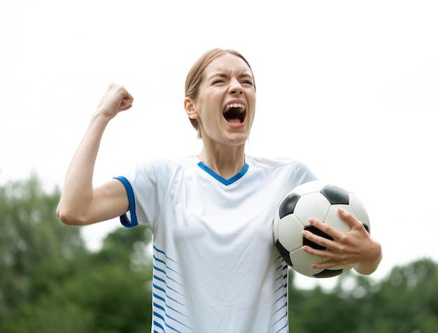 Mulher com tiro médio segurando uma bola