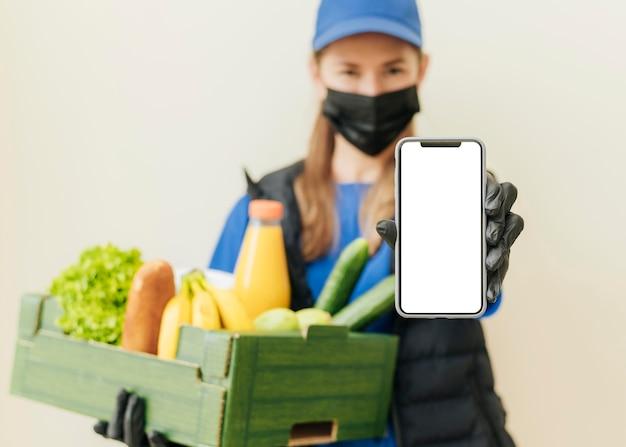 Mulher com tiro médio segurando uma caixa de comida