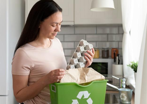 Mulher com tiro médio segurando uma caixa de ovos