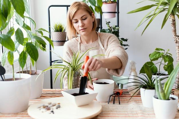 Mulher com tiro médio segurando uma ferramenta de jardinagem