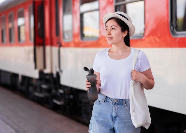 Mulher com tiro médio segurando uma garrafa de água