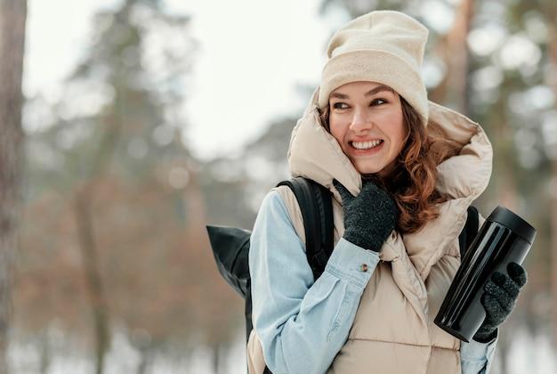 Mulher com tiro médio segurando uma garrafa térmica