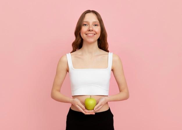 Mulher com tiro médio segurando uma maçã