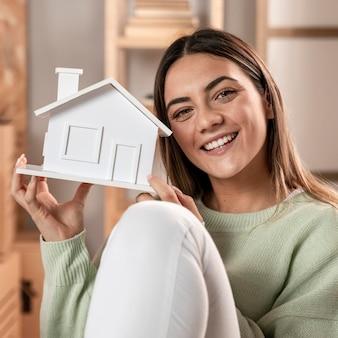 Mulher com tiro médio segurando uma pequena casa