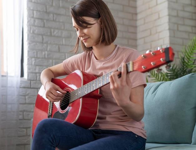 Mulher com tiro médio tocando guitarra no sofá