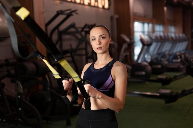 Mulher com tiro médio treinando na academia