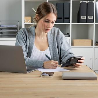 Mulher com tiro médio usando calculadora