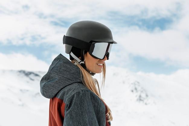 Mulher com tiro médio usando capacete de esqui