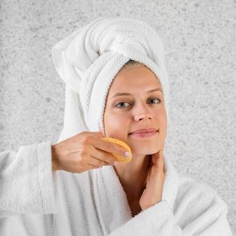 Mulher com tiro médio usando esponja amarela