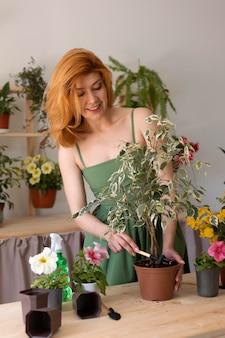 Mulher com tiro médio usando ferramenta de jardinagem