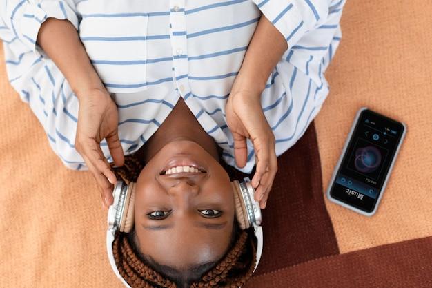 Mulher com tiro médio usando fones de ouvido na horizontal