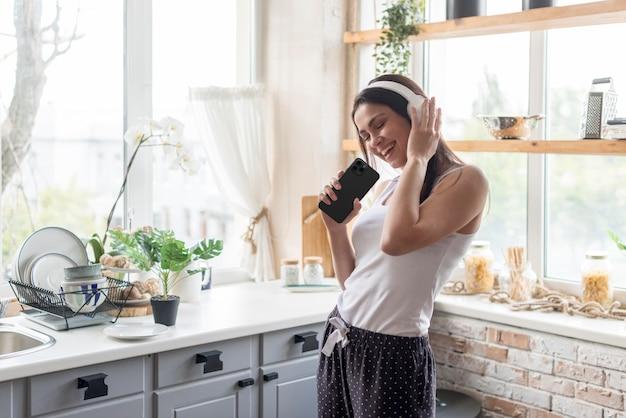 Mulher com tiro médio usando fones de ouvido