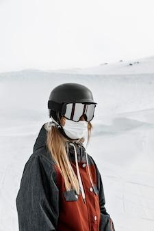Mulher com tiro médio usando máscara e óculos de proteção