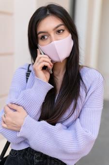 Mulher com tiro médio usando máscara rosa