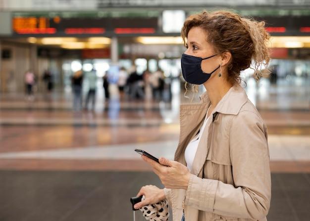 Mulher com tiro médio usando máscara