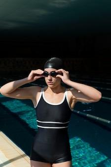 Mulher com tiro médio usando óculos e touca de natação