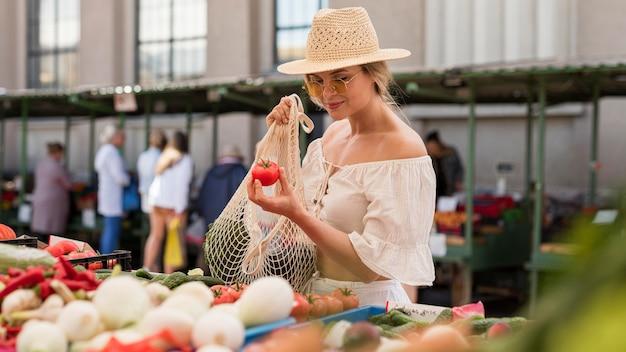 Mulher com tiro médio usando saco orgânico para vegetais
