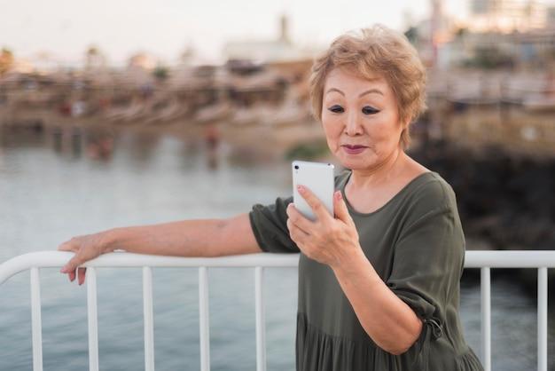 Mulher com tiro médio verificando o telefone