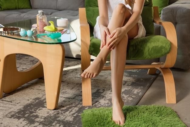 Mulher com toalha, fazendo sua rotina diária de cuidados com a pele em casa.