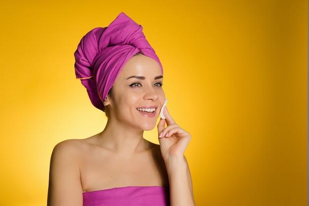 Mulher com toalha na cabeça após o banho limpa o rosto com algodão