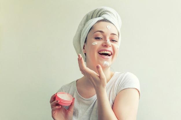 Mulher com toalha na cabeça com máscara nutritiva branca ou creme no rosto, fundo branco isolado