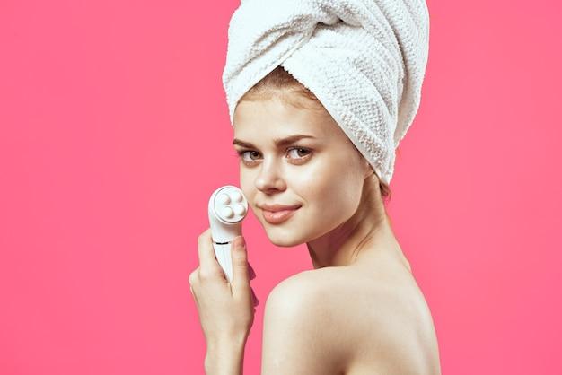 Mulher com toalha na cabeça, ombros nus massageador, saúde dermatologia