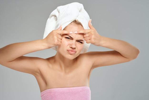 Mulher com toalha na cabeça problemas de pele facial dermatologia