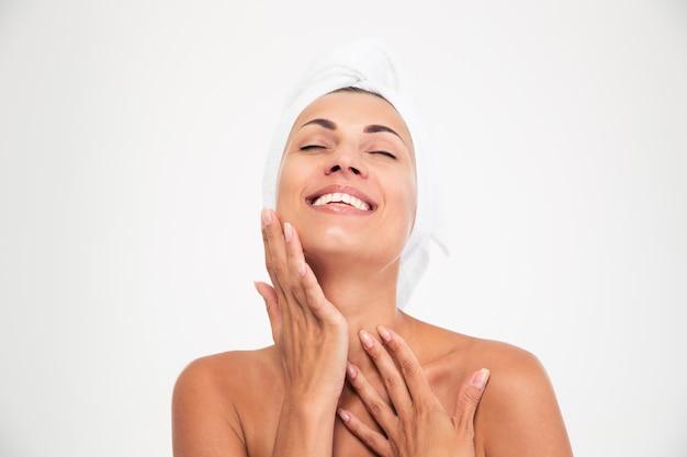 Mulher com toalha na cabeça tocando seu rosto