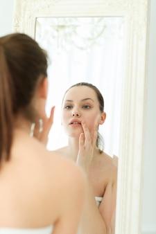 Mulher com toalha no corpo após o banho, olhando no espelho
