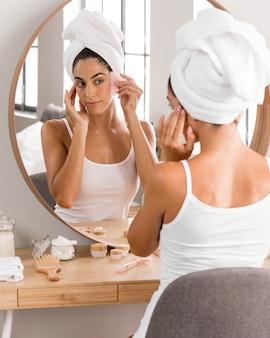 Mulher com toalha olhando no espelho