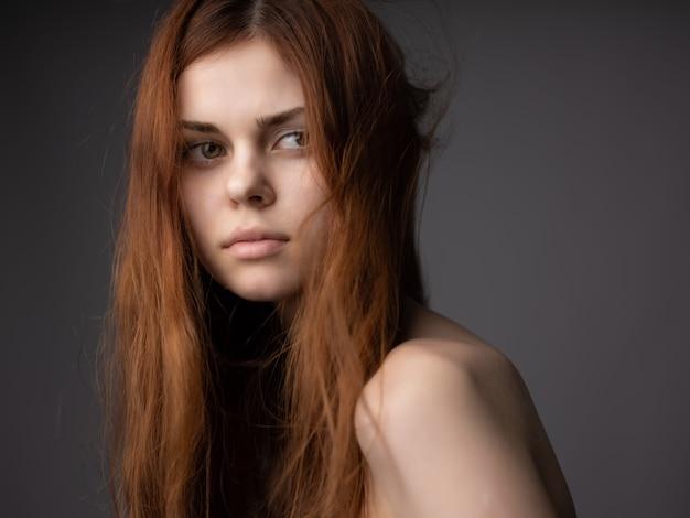 Mulher com torso nu e posando penteado com fundo escuro