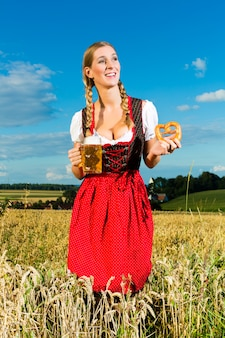 Mulher com tracht, cerveja e pretzel na baviera