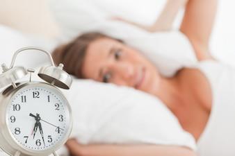 Mulher com travesseiro sobre a cabeça, como o despertador toca