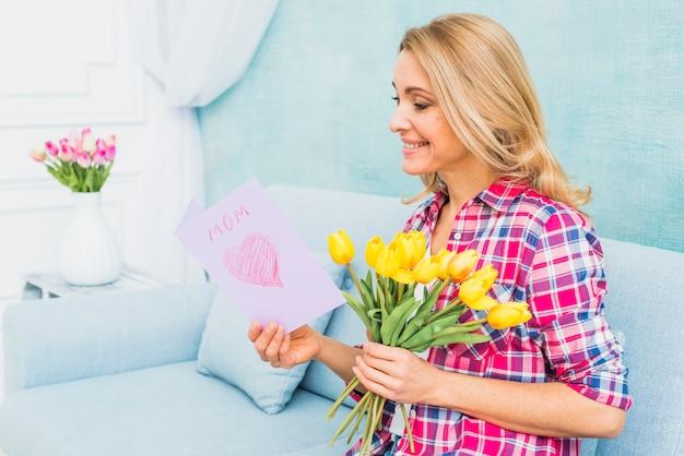 Mulher, com, tulips, ligado, sofá, leitura, cartão cumprimento