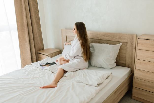 Mulher com túnica branca fica perto da janela e na cama no quarto do hotel