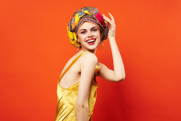 Mulher com turbante multicolorido decoração lábios vermelhos encanto parede vermelha de emoções.