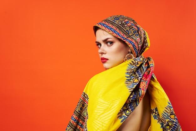Mulher com turbante multicolorido, lábios vermelhos e aparência atraente isolada