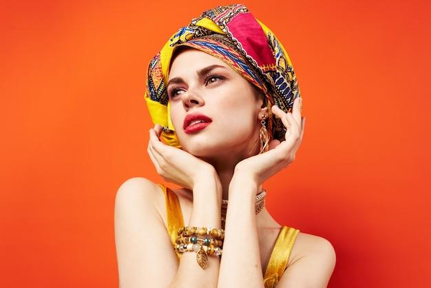 Mulher com turbante multicolorido na cabeça com metade da decoração de cosméticos isolada