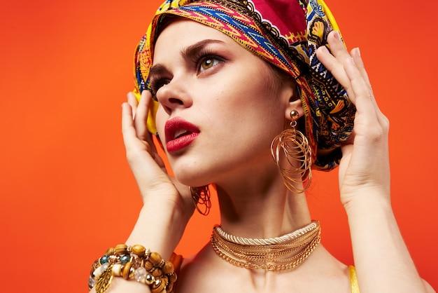 Mulher com turbante multicolorido na cabeça meio cosméticos decoração de fundo isolado