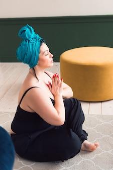 Mulher com turbante tradicional na cabeça fazendo ioga ou meditação