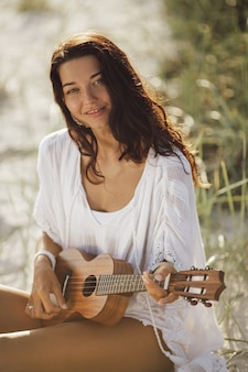 Mulher com ukulele durante as férias de verão na praia perto do mar