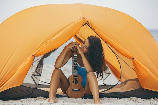 Mulher com ukulele na praia sob uma tenda laranja