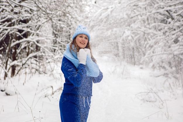 Mulher com um agasalho esportivo azul, luvas brancas e lenço fica no inverno em uma floresta coberta de neve
