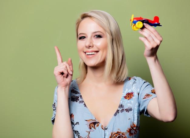 Mulher com um avião de brinquedo imagina uma viagem de verão