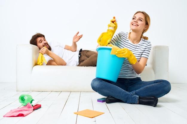 Mulher com um balde em luvas de borracha em casa, marido deitado no sofá limpando
